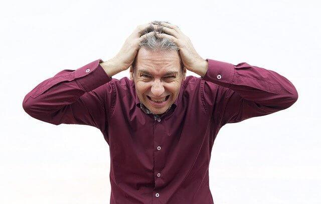 Mann mit weinrotem Hemd rauft sich die Haare über seine vermutlich psyschichen Ursachen der Potenzstörung