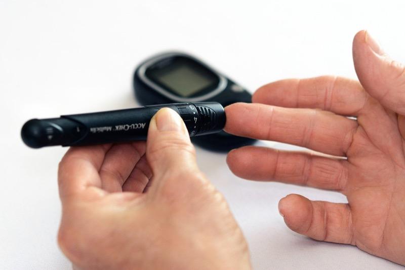 Ein Blutzucker-Messtift misst den Blutzuckergehalt im rechten Mittelfinger