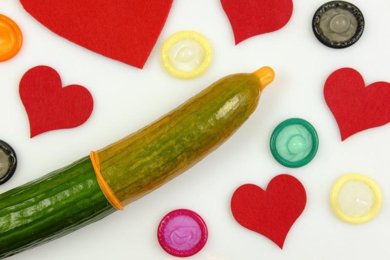 Bunte Kondome und rote Herzen zu einem Kondom auf einer Gurke als Symbol für einen Penis
