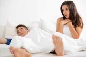 Junge Frau ist erstaunt über Morgenlatte ihres noch schlafenden Partners