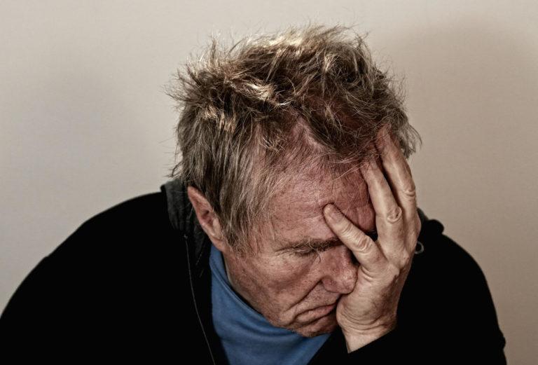 Gestresster Mann ist hält verzweifelt sein Gesicht in seiner linken Hand
