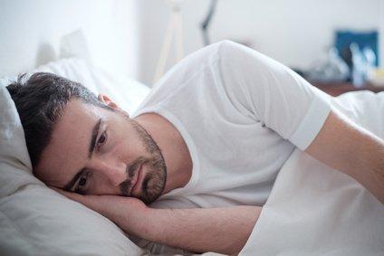 Mann mit Impotenz liegt gedankenverloren auf der rechten Körperseite im Bett